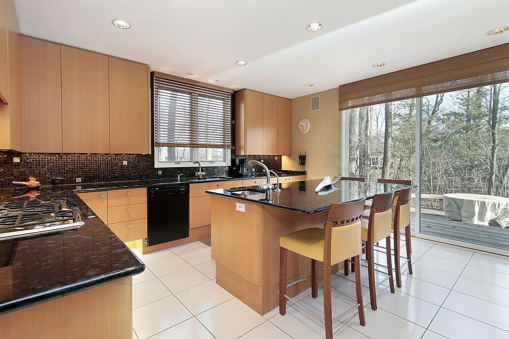 Black Countertops Contrast With Brightly Toned Smooth Wood Cabinets And  White Tile Floor In This Kitchen