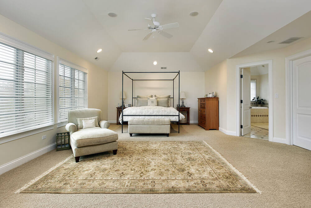 Large But Sparsely Furnished Bedroom With Off White Walls And Beige Carpeting