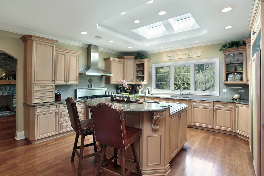 The light wood used in this kitchen features a unique tone that fits perfectly between the white ceiling with sky light, and the darker hardwood floor.