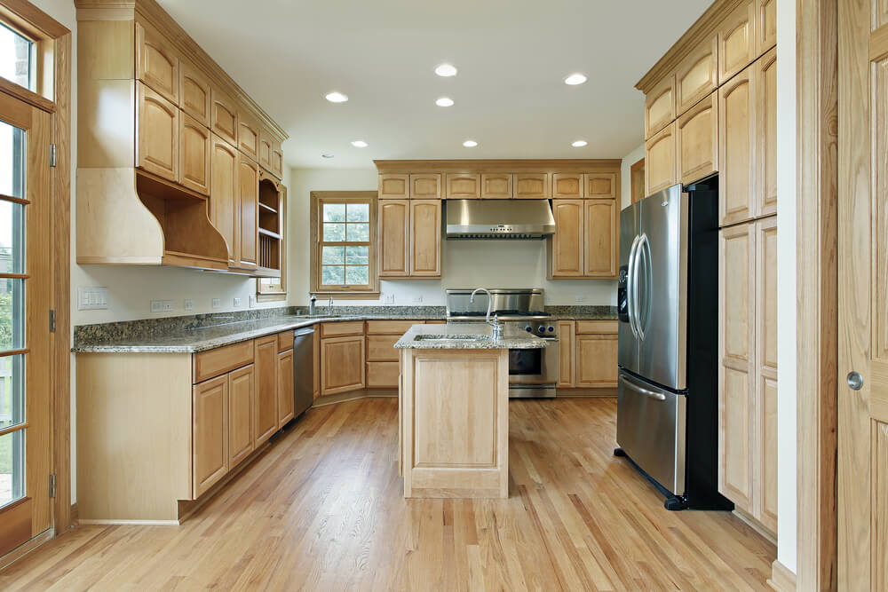 Matching the tone of the hardwood floor, this kitchen contrasts brushed aluminum appliances with a multitude of light wood cabinets.