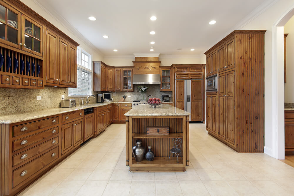 Grainy Wood With Ornate Cabinet Design Describes This Large Kitchen With Long Matching Island