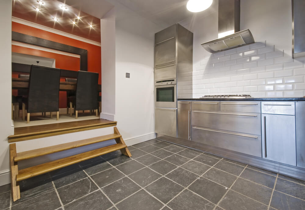 Small Industrial Kitchen Entirely In Stainless Steel With White Wall Steps Lead To Separate Dining