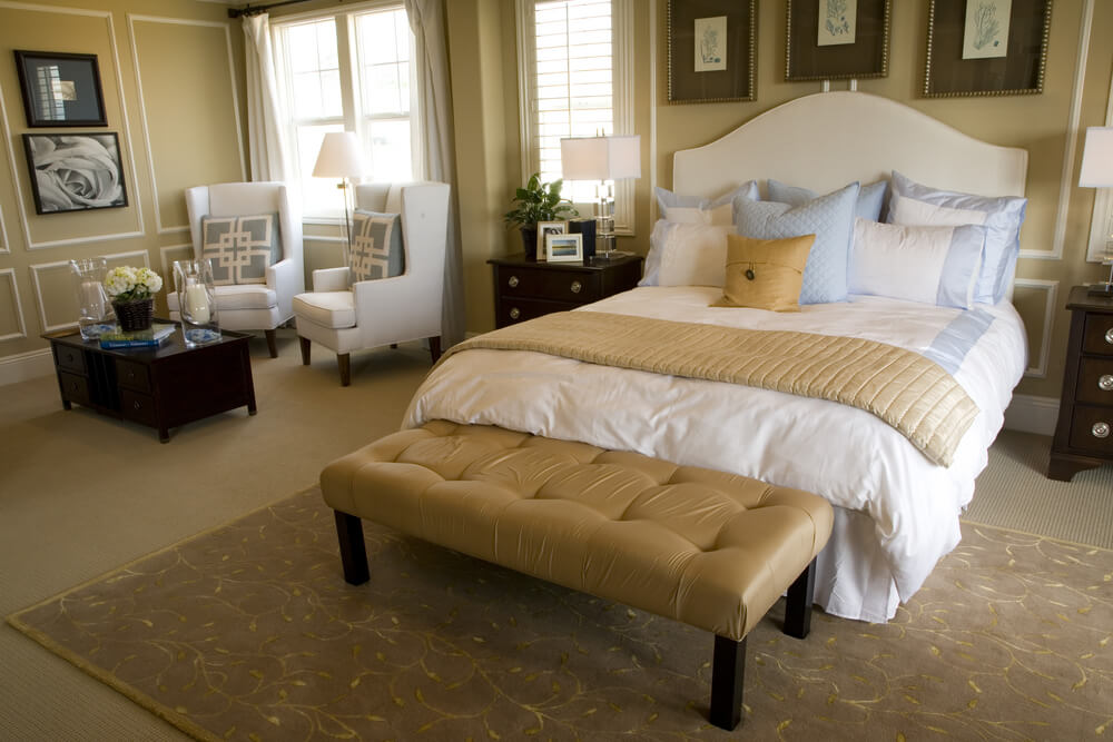 Ottoman White Bed And Floral Patterned Rug Over Beige Carpeting