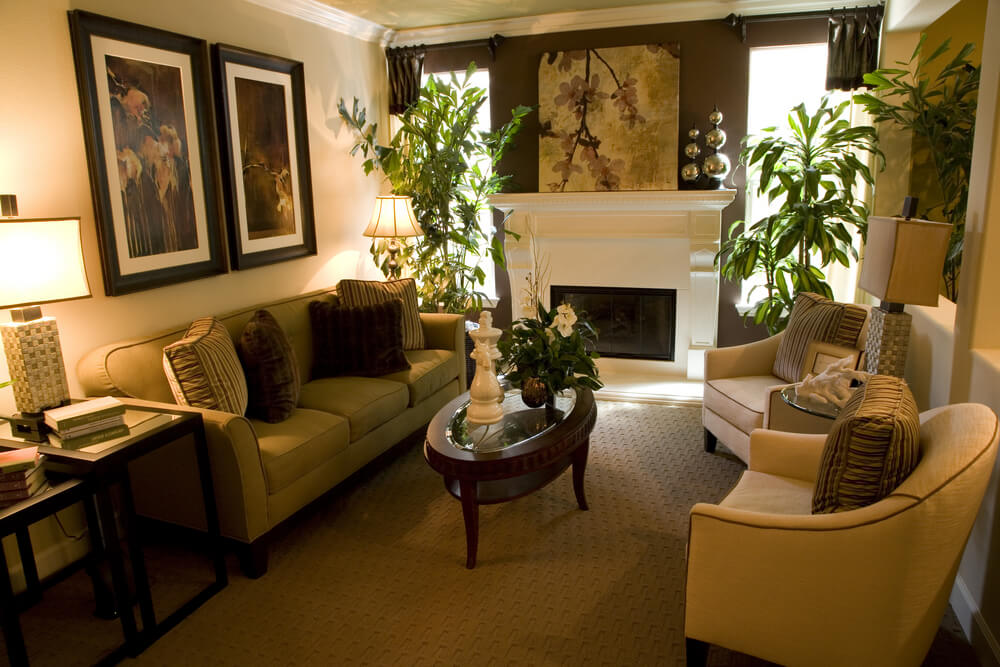 Darker hued living space in this room featuring brown outer wall, carpeting and tables, with light colored chairs and light green couch.