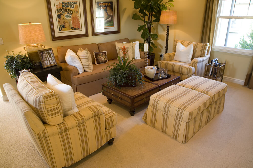 This living room features wall to wall carpeting and a unique suitcase-styled coffee table.