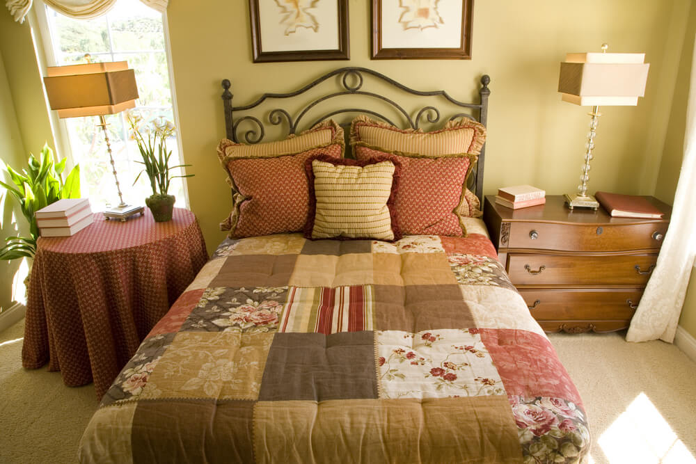 bedroom featuring a country style with patchwork blanket patterned pillows and table covering