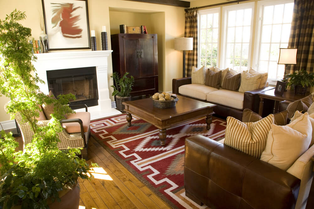 Natural hardwood flooring in this room is aided by a brightly colored Southwestern rug, combination leather-and-cloth couches, and a claw-foot square coffee table.