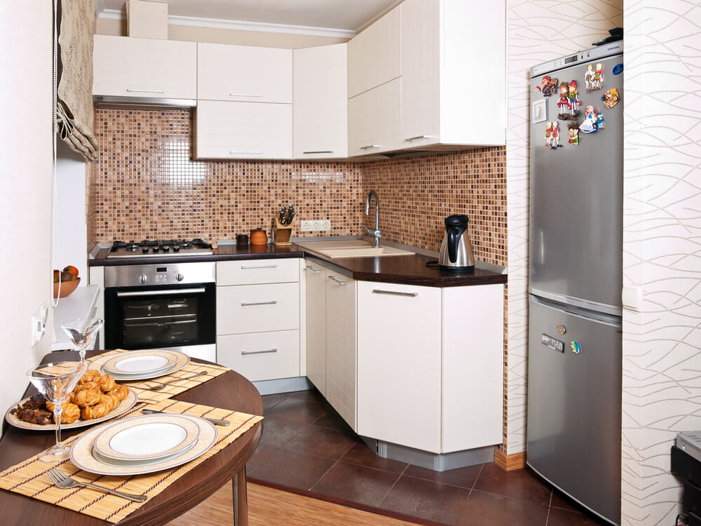 small apartment kitchen with white cabinets and patterned tile back splash small semi circle