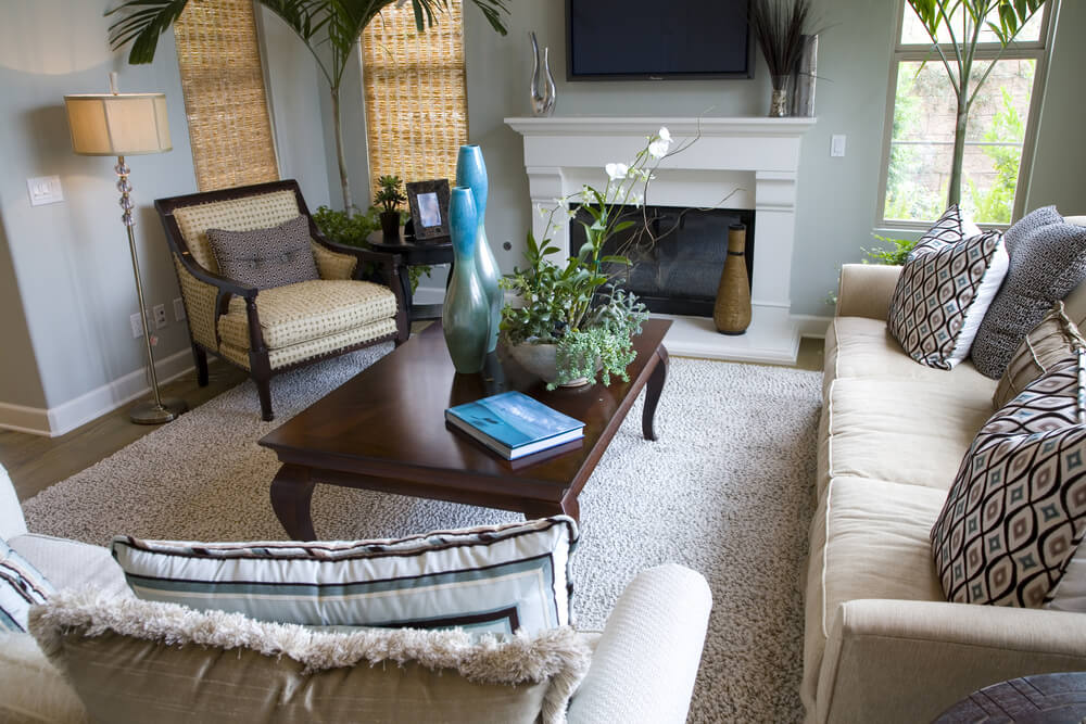Light shag carpeting and couches, bright patterned throw pillows, and a white fireplace add light to this room while a dark, old fashioned legged coffee table and unique armchair fill it out.