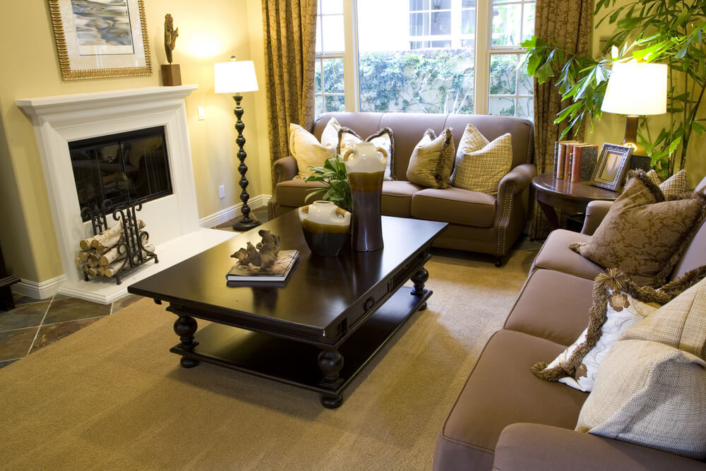 Easter yellow walls help lighten this living room set over a stone tile floor with  beige rug.