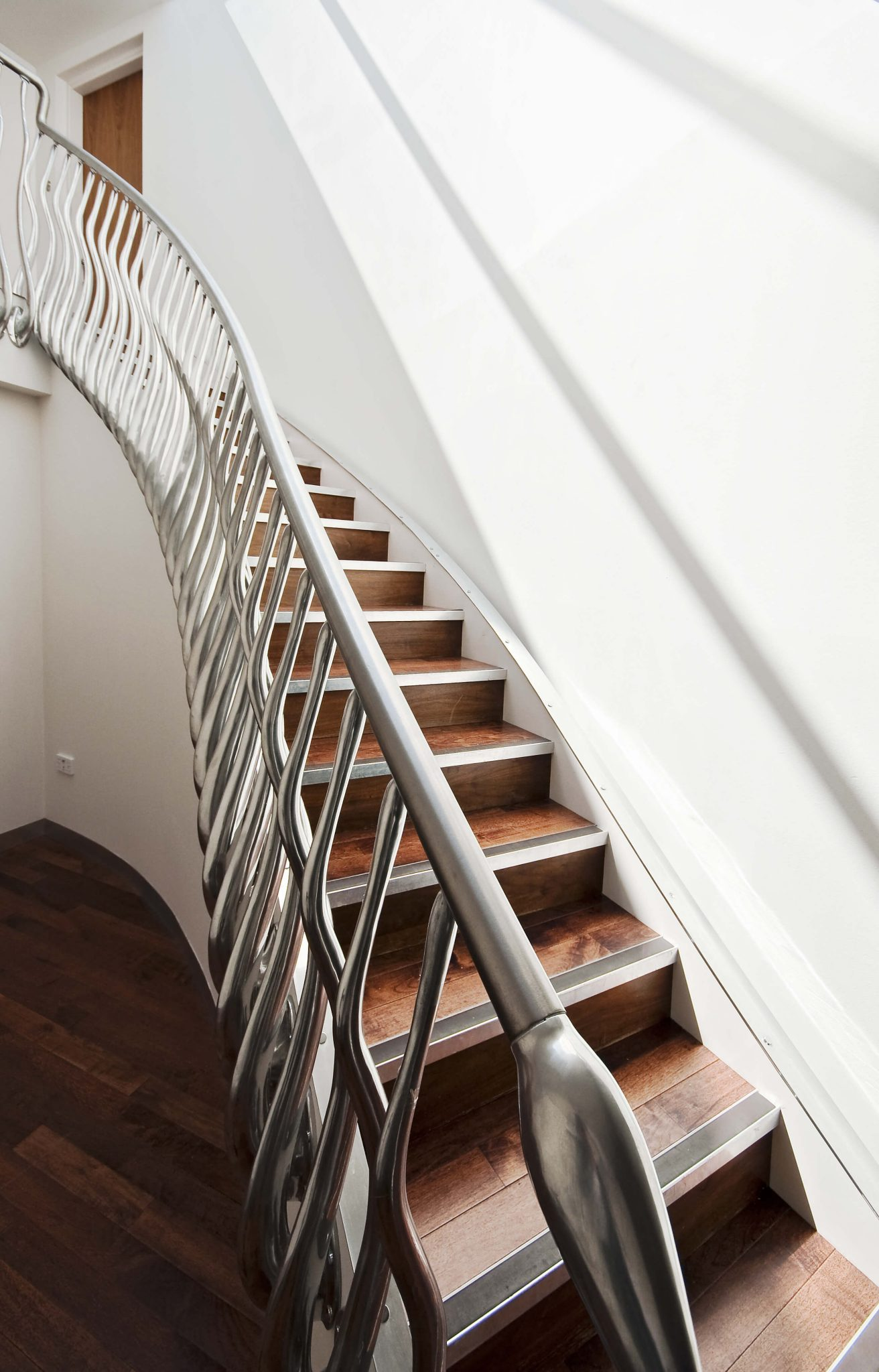 Wood steps encased in closed stringer.  The ornate metal handrail and baluster make this staircase stand out.