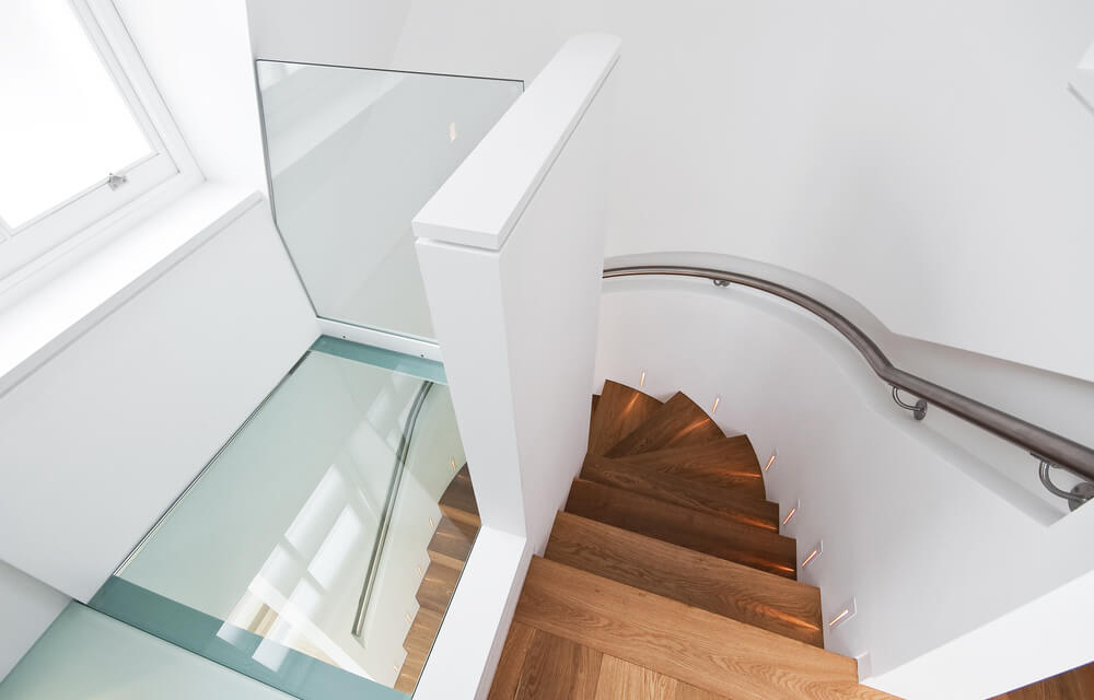 View of modern staircase from above.  Stairs are wood with metal handrail.  Lower portion of stairs look through glass ceiling.