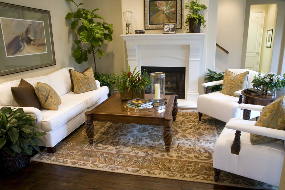 Pure white furniture set in this room, comprised of two chairs and a couch, match the fireplace.