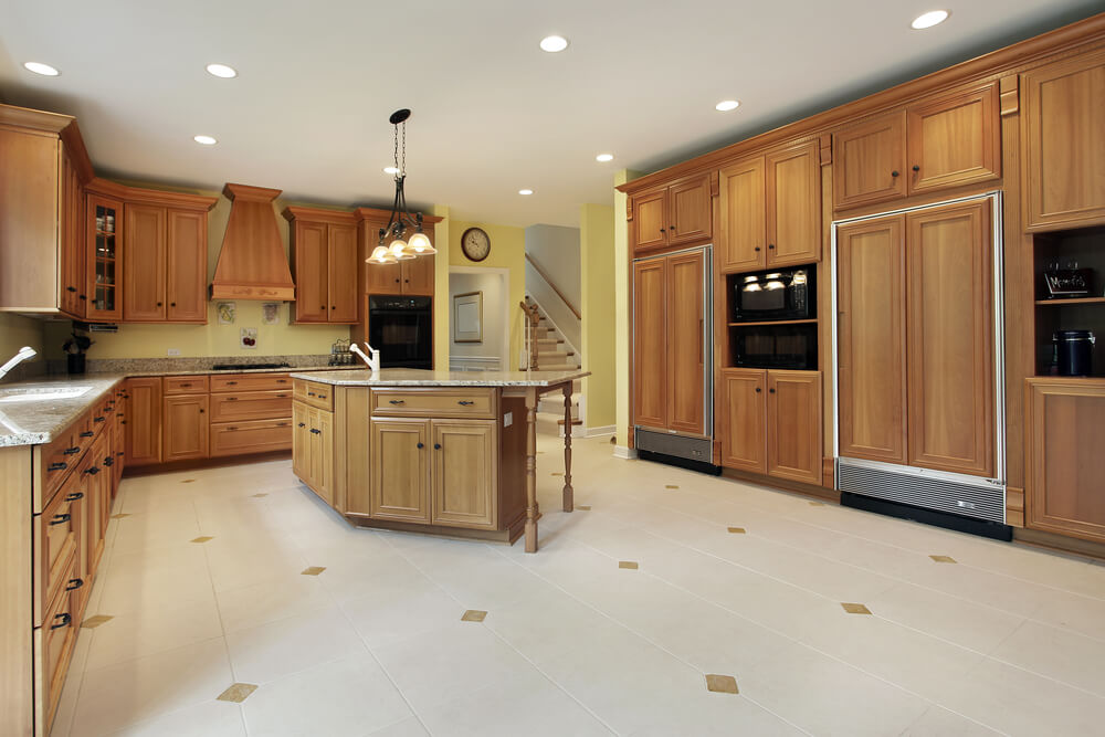 Natural Wood Cabinets Wrap Around Three Walls In This Large Kitchen Space Which Also Includes A