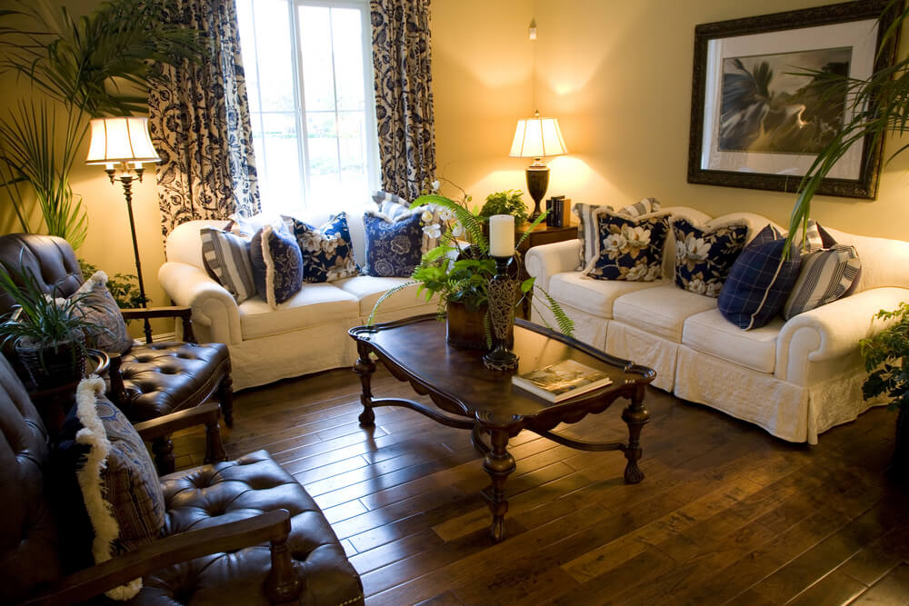 Room filled with rich dark tones on the filigreed coffee table and stuffed leather armchairs.