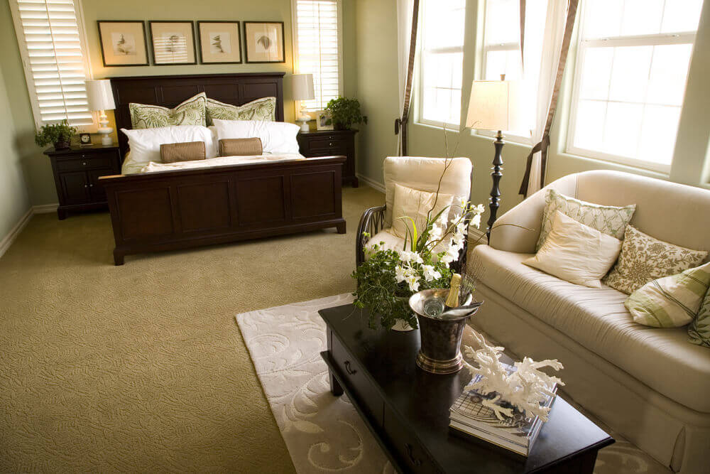 heres a combination living room and sleeping area with a simple light colored couch and