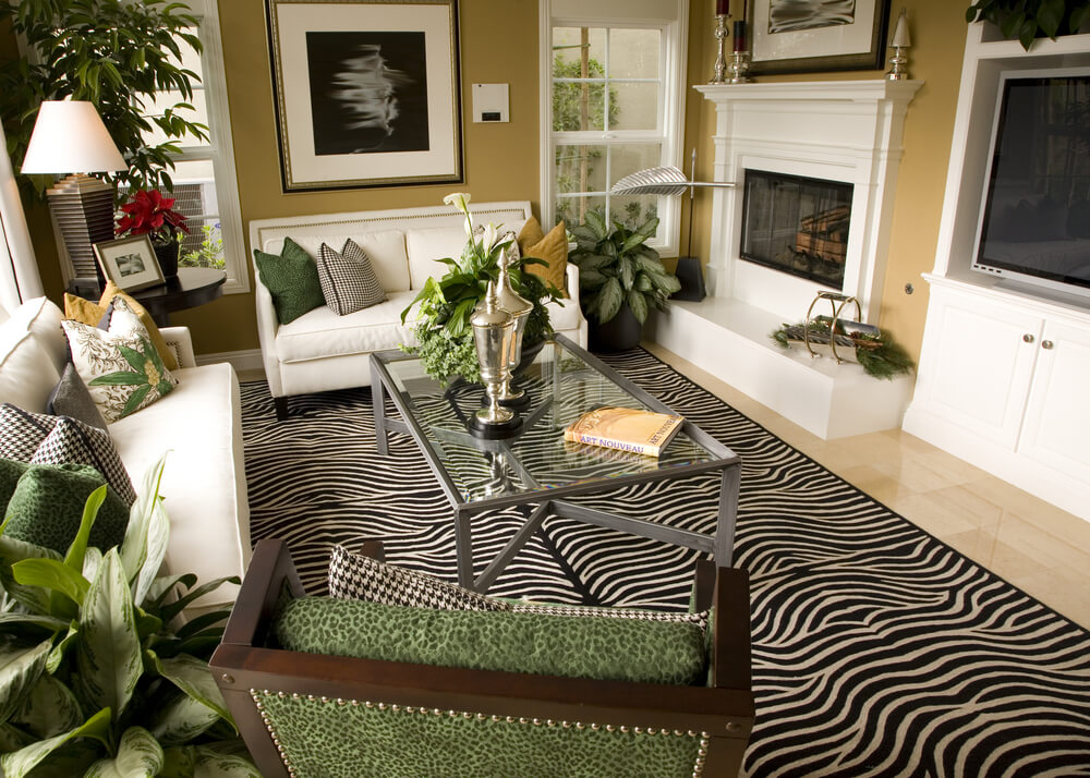 A study in contrasts, this living room features white entertainment unit, fireplace, and couches, gathered around a zebra print rug, metal and glass coffee table, and forest green armchair.