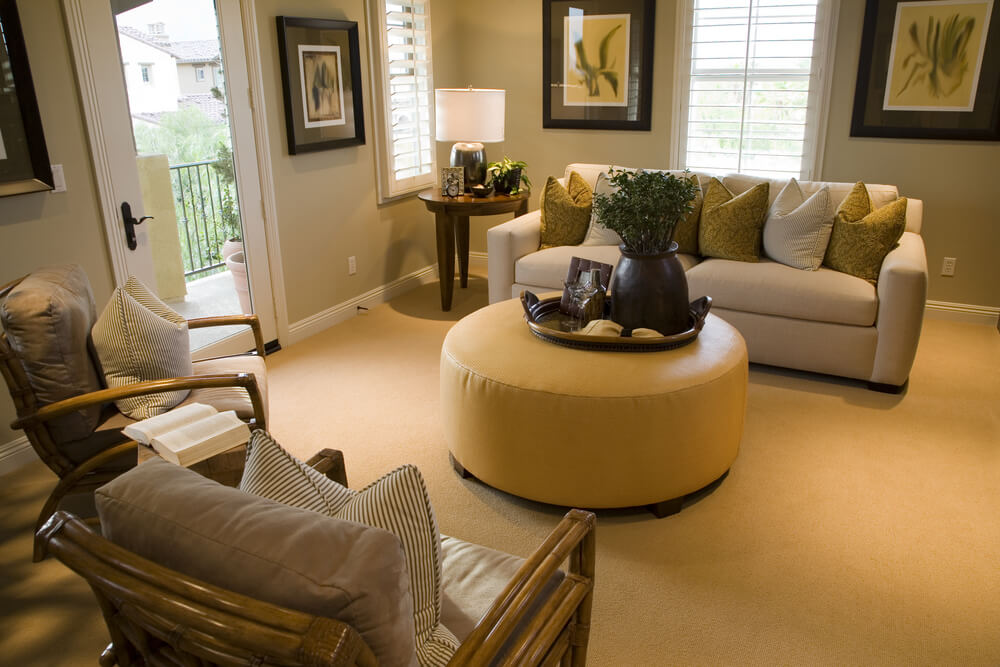 Living room centered around a large circular yellow ottoman.