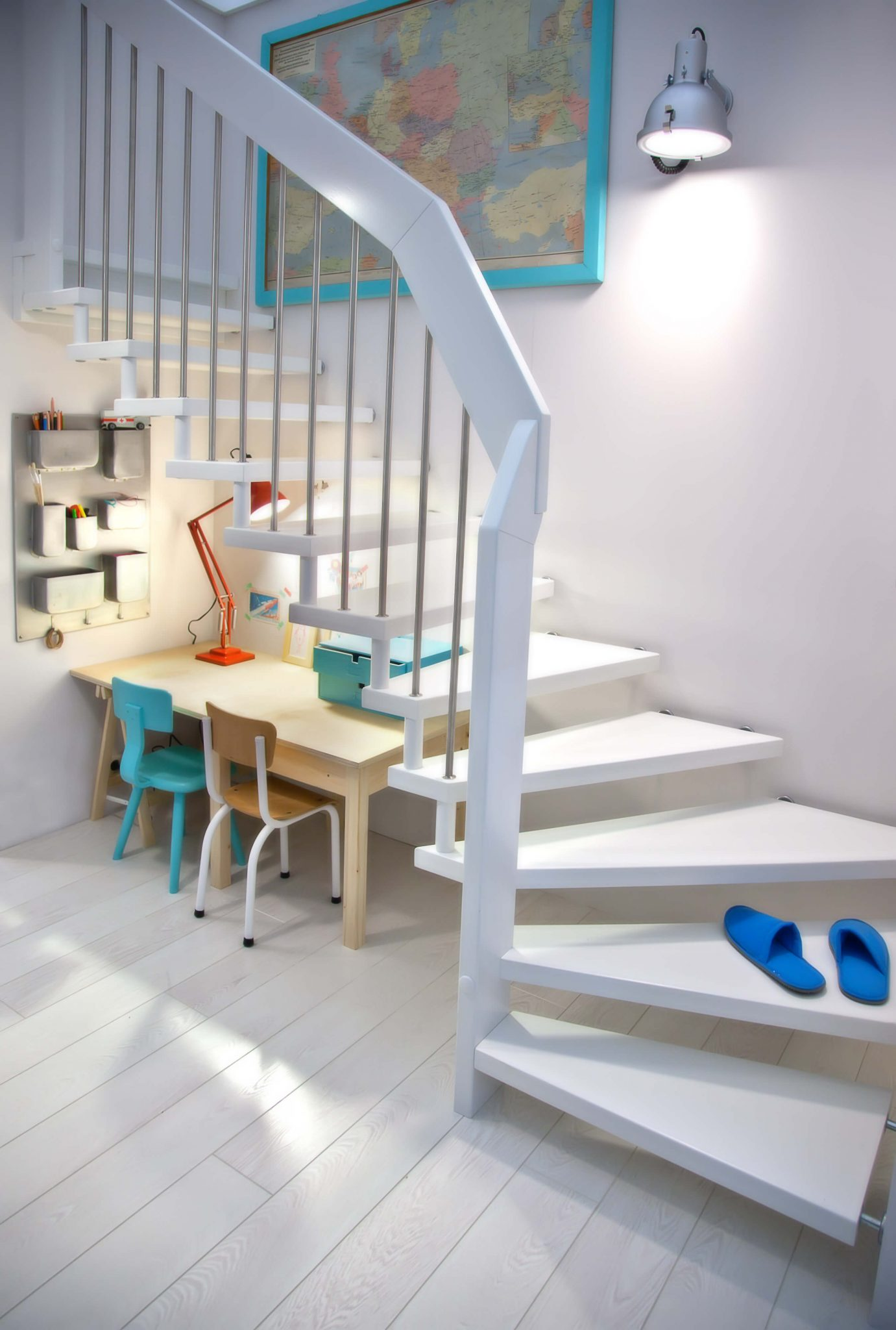 Interesting white staircase with no outside stringer floats above children's play and desk area.