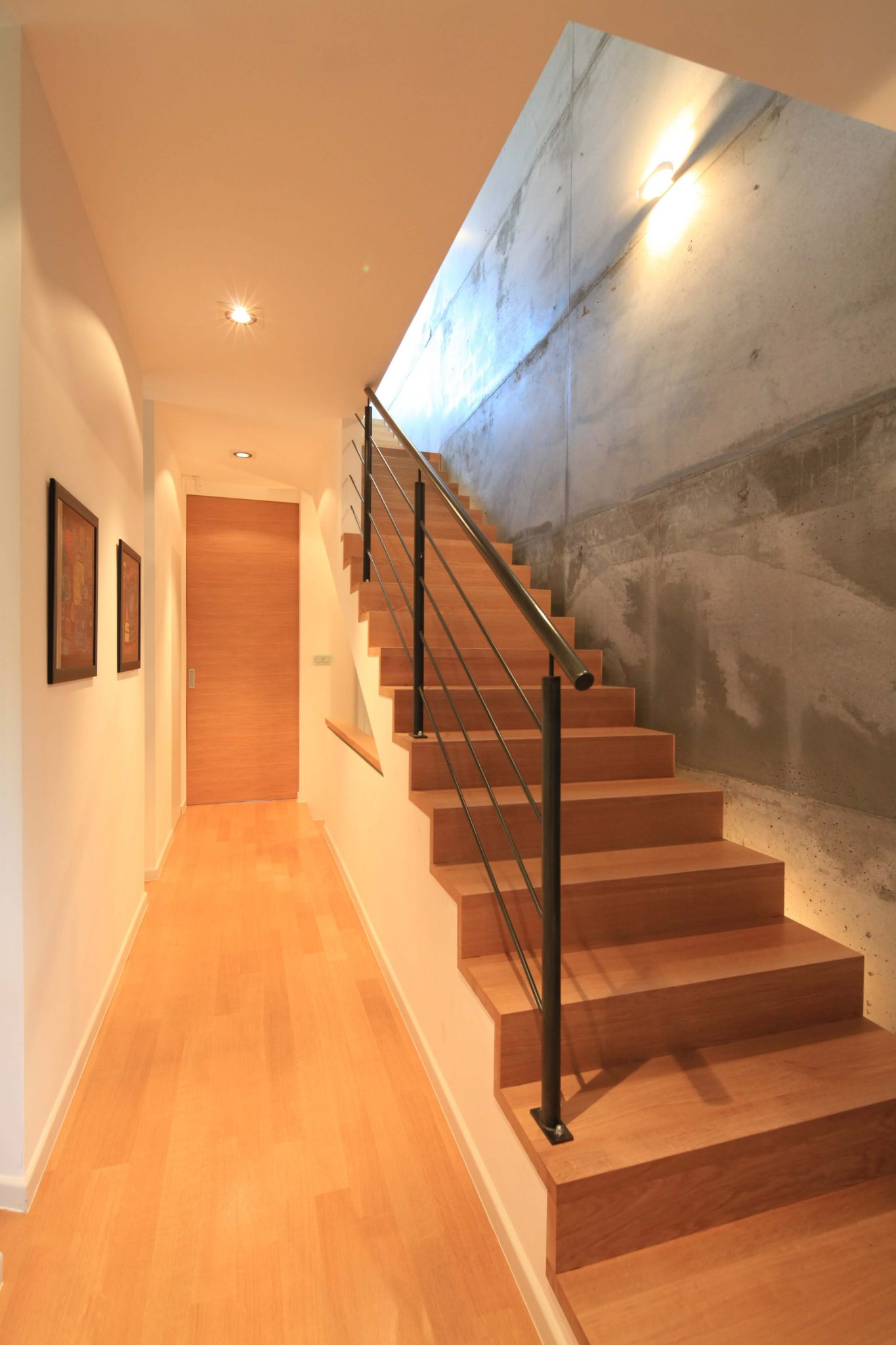 Straight staircase with black metal baluster set against a concrete wall.
