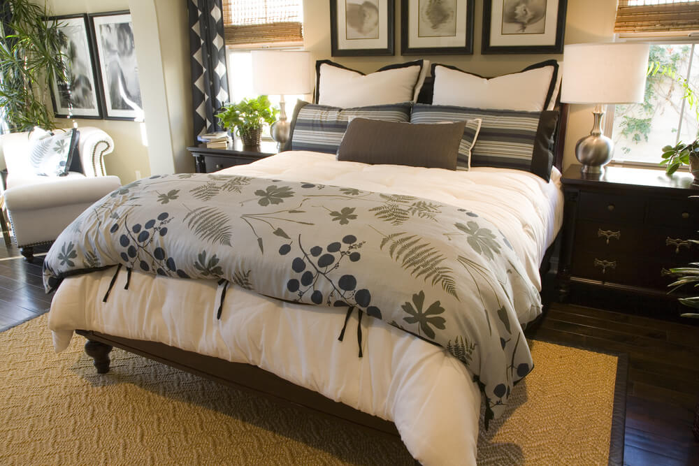 nature focused blanket in this cozy bedroom complements the plant life surrounding dark wood furniture and