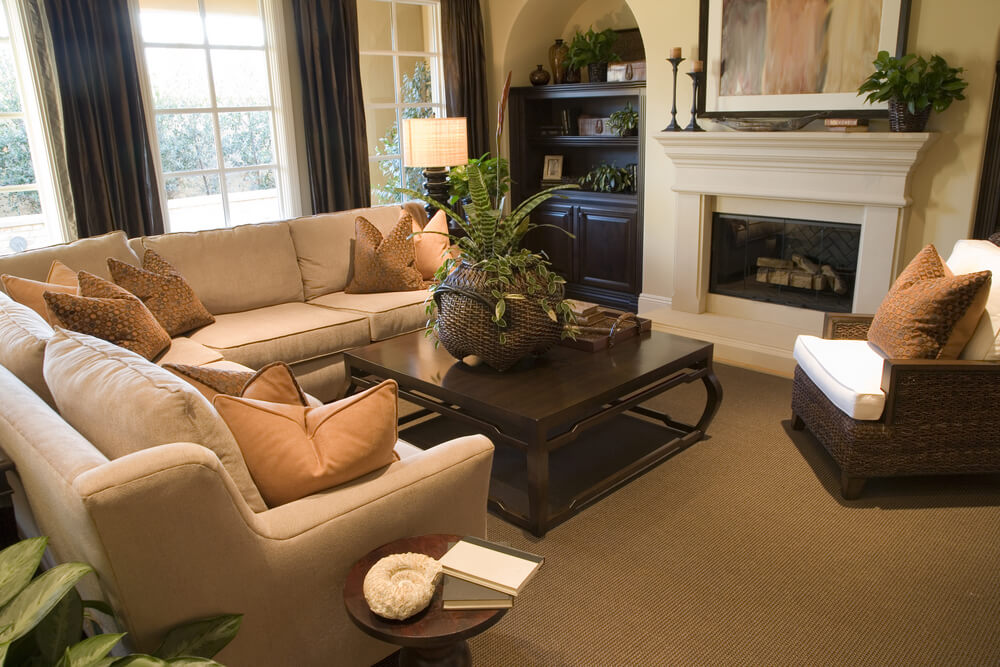 Large salmon colored L shape couch embraces this cozy living room, featuring a wicker armchair and white fireplace.