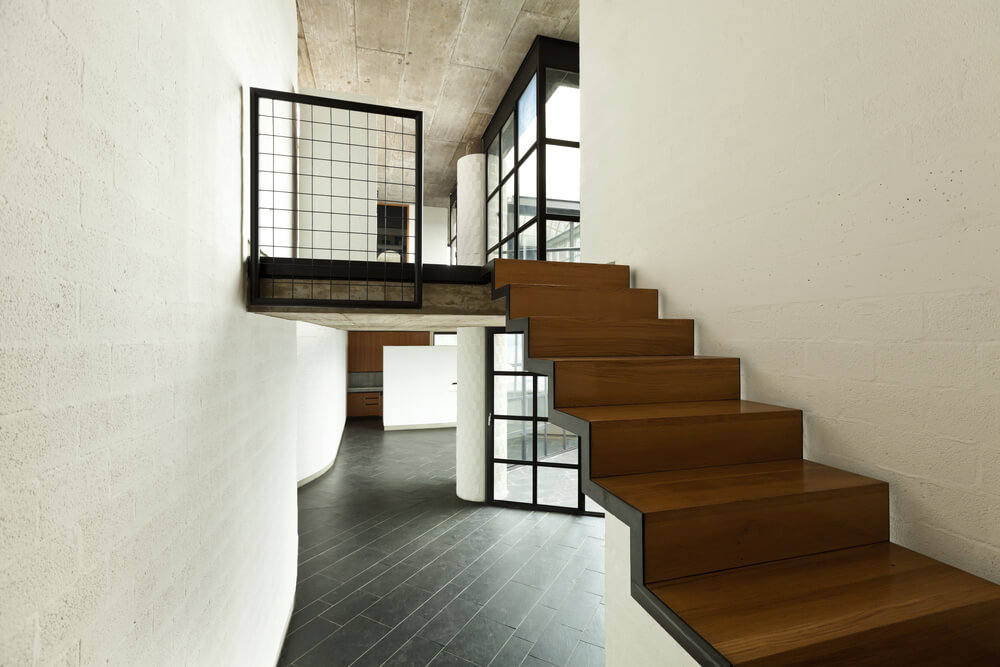 Open black metal thin stringer supports wooden treads (steps) and risers with this modern staircase that appears to float.