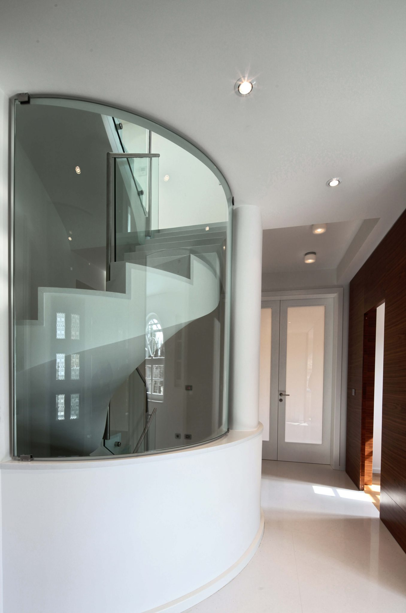 Spiral staircase inside glass stairwell in the middle of large foyer of a luxury home.