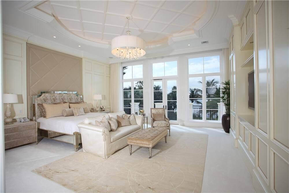 Large master bedroom with custom white paneling on walls, custom tray ceiling and one wall entirely windows with glass door to private balcony overlooking the ocean.