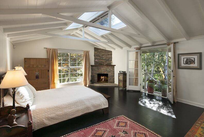 White cathedral ceiling with exposed white wood beams and skylights make  this large cottage bedroom stand