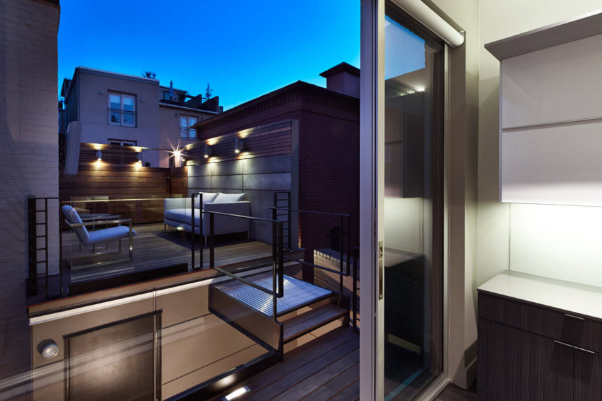 View from inside kitchen over rooftop deck. Small metal bridge, railings, and patio furniture are seen through large glass entryway.