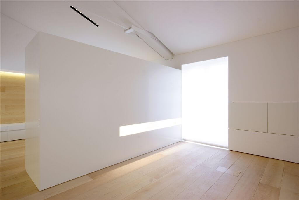 Far end of living room, with dividing wall featuring built-in lighting and hidden storage.
