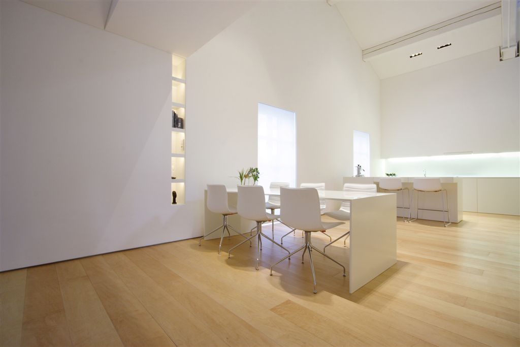 Angled view of kitchen and dining area, highlighting in-wall bookshelf with built in lighting, all-white furniture, and projection wall above sink.