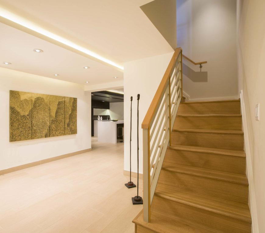 Staircase from main floor, opening to wide hallway with light hardwood flooring, embedded lighting in the drop ceiling, and large art piece on wall.