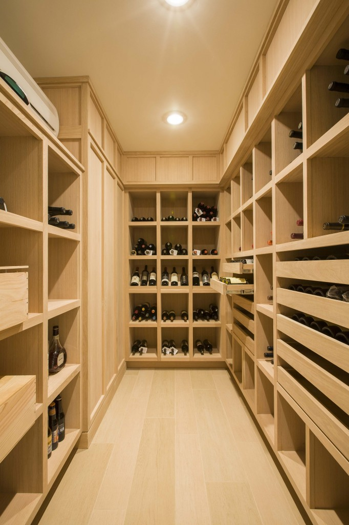Wine cellar featuring extensive use of light natural wood matching the flooring throughout basement level.