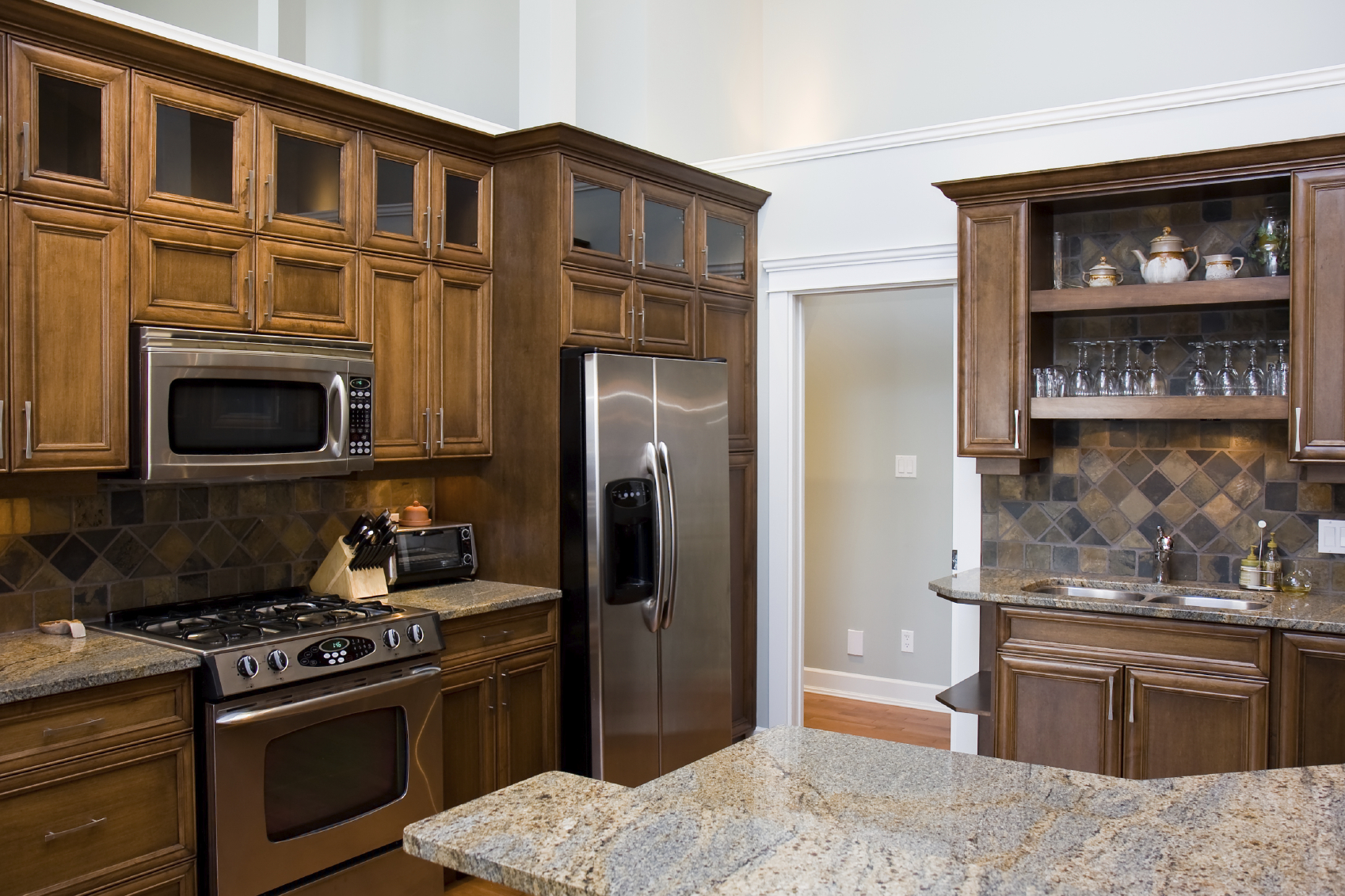 wood, with light grey marble countertops and aluminum appliances