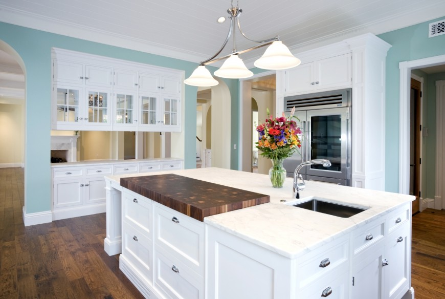 Vibrant Light Blue And White Dominates This Kitchen Featuring Bright Cabinetry Over Natural Hardwood Flooring