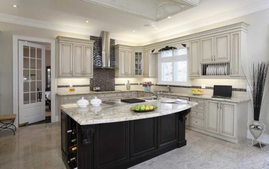Light Toned Kitchen Features Immense Black Island With Built In Wine Rack  And Marble Countertop