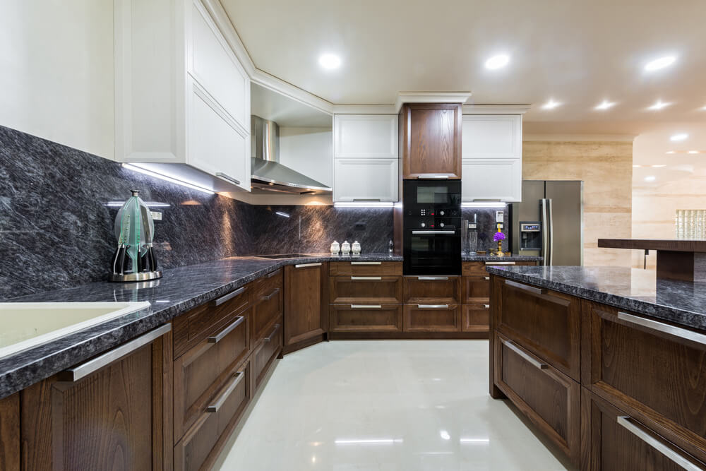 contemporary kitchen with lower dark brown cabinets and white upper