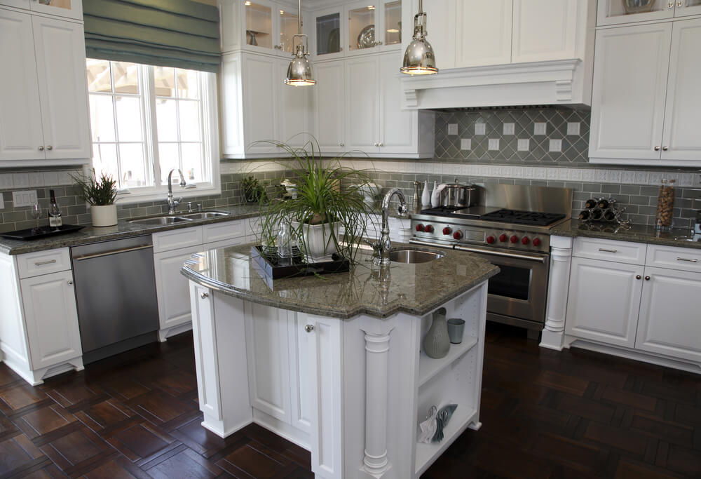 Detailed Dark Wood Flooring Under White Cabinetry With Dark Marble Countertops Provide The Theme In
