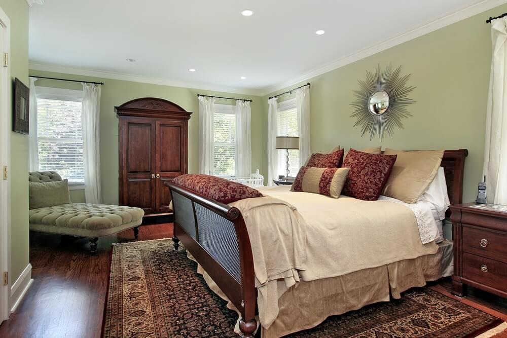 this bedroom combines light green walls with dark wood flooring matching the bed frame
