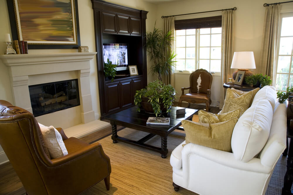 rich leather on two chairs in this room stand out next to white couch