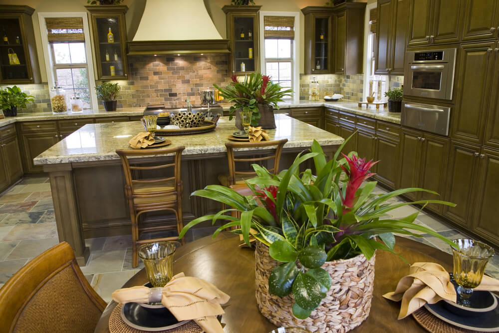 Lush earth tones fill this kitchen, with dark brown cabinetry, glass