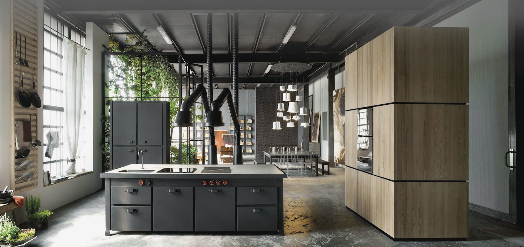 The kitchen here features a unique use of industrial style space, with black piping connecting island to ceiling, with large natural wood freestanding wall holding oven to the right. Outer wall features built in dish rack, ceiling height windows.