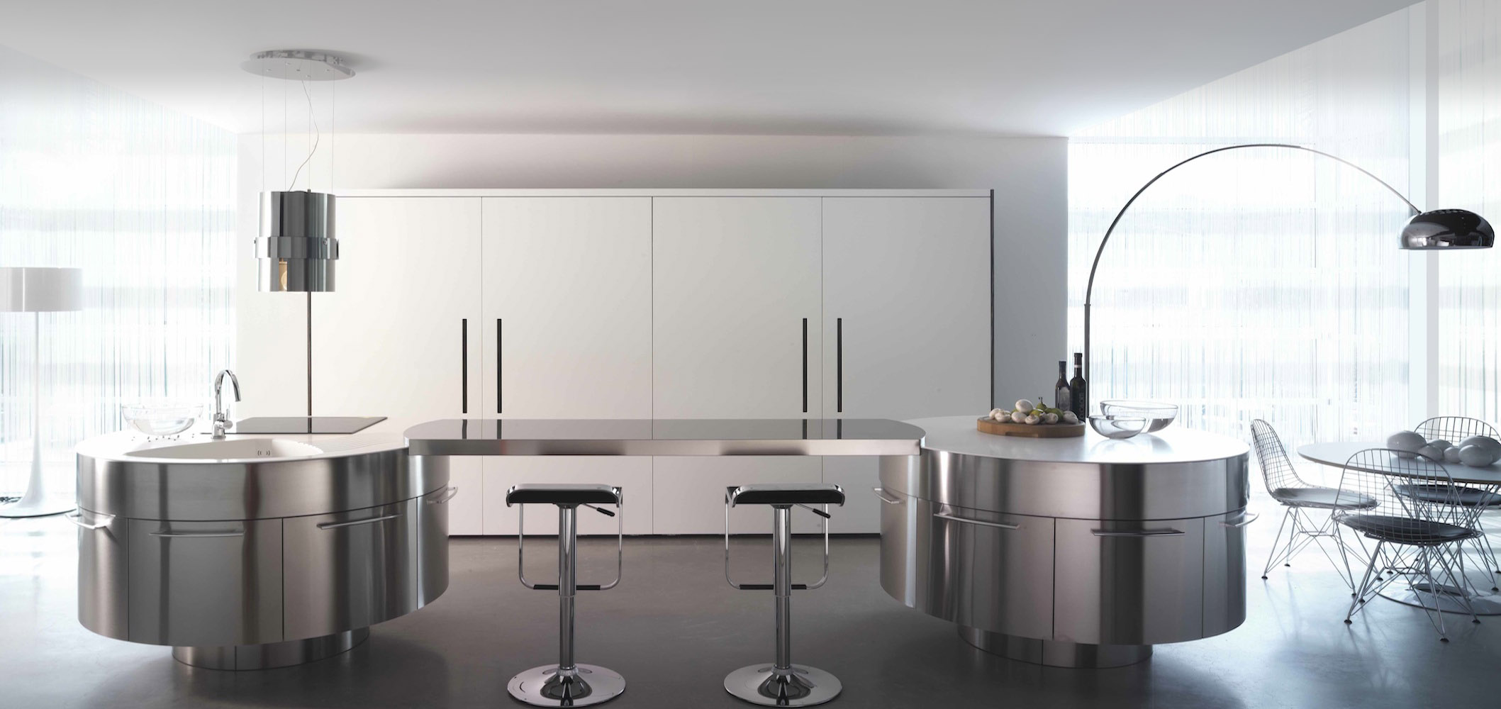 Twin circular metallic islands are connected via metal countertop bridge in this modern kitchen. Large white flush cabinet doors stand over dark flooring, with floor to ceiling windows in background.