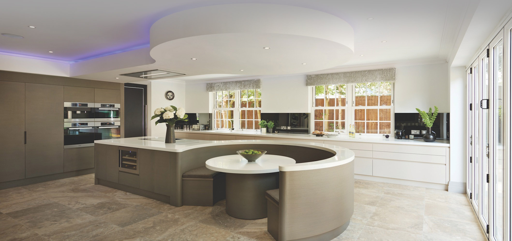 Ceiling hidden purple accent lights highlight ceiling detail mirroring the large island and circular dining booth in this large kitchen featuring light browns and whites on all surfaces.