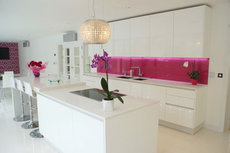Kitchen fully decked out in glossy white texture, from floor to ceiling, features unique pink backsplash lit from beneath cabinets.