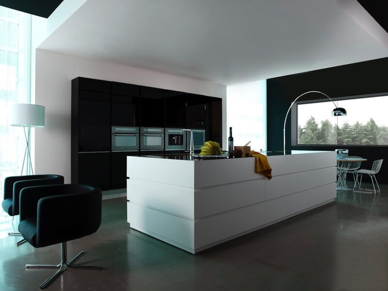 This kitchen is part of a large open space, defined by a white overhang. White island with black countertop sits across black panel wall featuring appliances, with dining area in background.