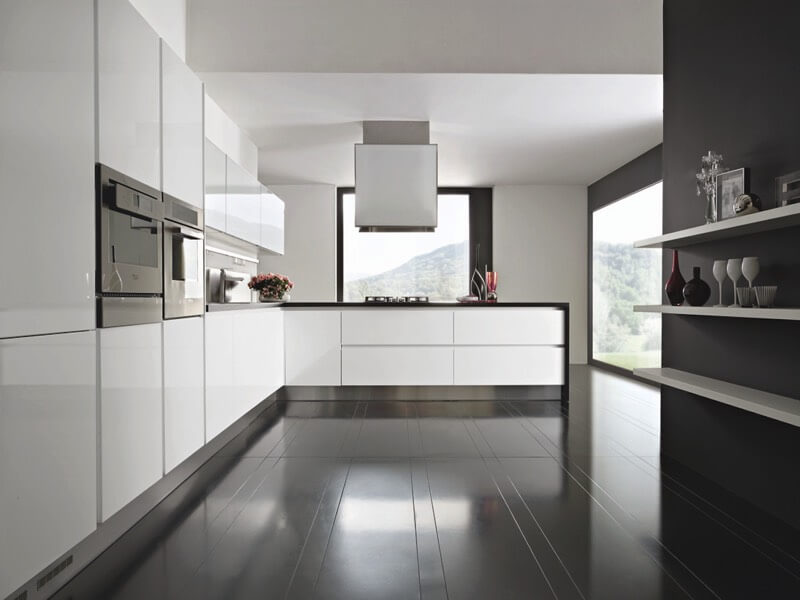Another great example of high contrast between black flooring and glossy white cabinetry appears in this kitchen. White shelving on black walls, plus black countertops, continue the theme.