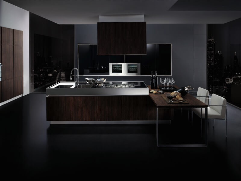 Dark and rich describes the tones in this kitchen: black flooring meets dark wood paneling with metallic textures between. Dining table extends from island featuring range and sink.